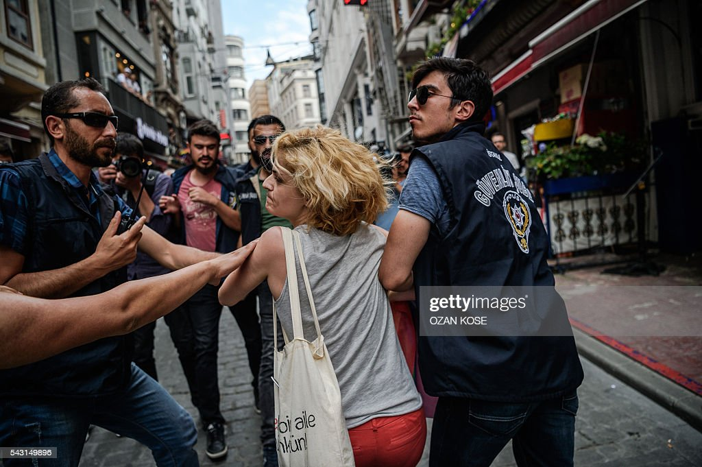 Riot police officers detain a LGBT demonstrator during a rally staged by the LGBT community on Istiklal avenue in Istanbul on June 26, 2016. Riot police fired tear gas and rubber bullets to disperse protesters defying a ban on the city's Gay Pride parade. Authorities in Turkey's biggest city had banned the annual parade earlier this month citing security reasons, sparking anger from gay rights activists. KOSE