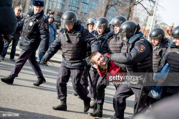 Riot police officers detain a man during an unauthorised anticorruption rally in central Moscow on March 26 2017 Thousands of Russians demonstrated...
