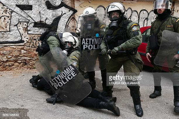 Riot police officers detain a protestor near the Agriculture ministry in Athens during a demonstration of farmers against the pension reform on...