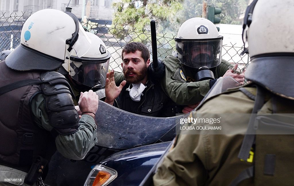 Riot police officers detain a protestor near the Agriculture ministry in Athens during a demonstration of farmers against the pension reform on February 12, 2016. Fears that Greece will exit the eurozone, a 'Grexit', could revive if Greek authorities do not come up with 'credible' reforms, notably on pensions, a senior IMF official said February 11, 2016. / AFP / LOUISA GOULIAMAKI
