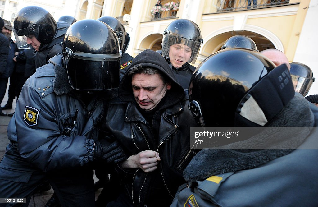 Riot police officers detain an opposition activist in central St. Petersburg on March 31, 2013, during an unauthorized protest rally of opposition activists to defend the article 31 of the Russian constitution which guarantees freedom of assembly. Russian opposition activists call on authorities to respect the right to organize rallies every 31st of a month, which often leads to arrests by the police. AFP PHOTO / OLGA MALTSEVA