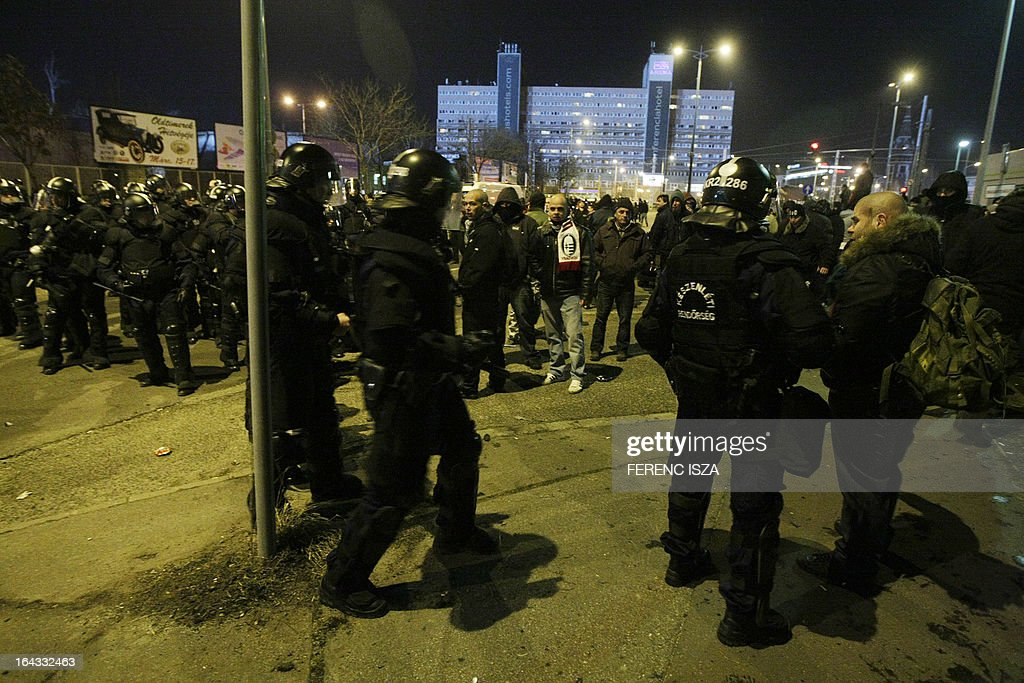 Riot police officers face-off with Hungarian fans outside of the Puskas stadium after the Hungary vs Romania FIFA 2014 World Cup qualifying football match in Budapest, on March 22, 2013. FIFA ordered Hungary to play the 2014 World Cup qualifier match behind closed doors after fans hurled anti-Semitic abuse during a friendly match with Israel in August 2012. AFP PHOTO / FERENC ISZA