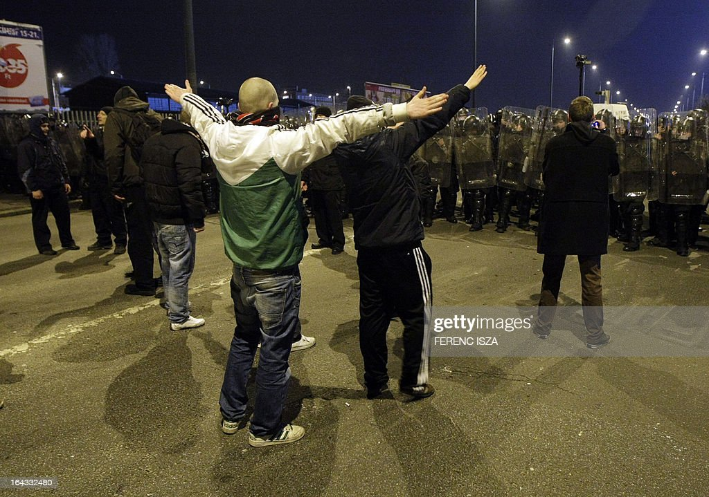 Riot police officers face-off with Hungarian fans outside of the Puskas stadium after the Hungary vs Romania FIFA 2014 World Cup qualifying football match in Budapest, on March 22, 2013. FIFA ordered Hungary to play the 2014 World Cup qualifier match behind closed doors after fans hurled anti-Semitic abuse during a friendly match with Israel in August 2012.