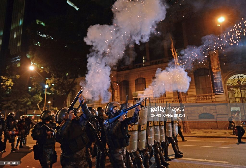 Riot police officers fire tear gas at violent demonstrators after clashes erupted following a march by Brazilian workers in Rio de Janeiro on July 11, 2013 in a day of industrial action called by major unions to press demands for better work conditions. Demonstrators on Thursday blocked roads and staged protest rallies across the country on the 'National Day of Struggles' which was called by the country's five leading labour federations during last month's mass street protests to demand better public services and an end to endemic corruption.