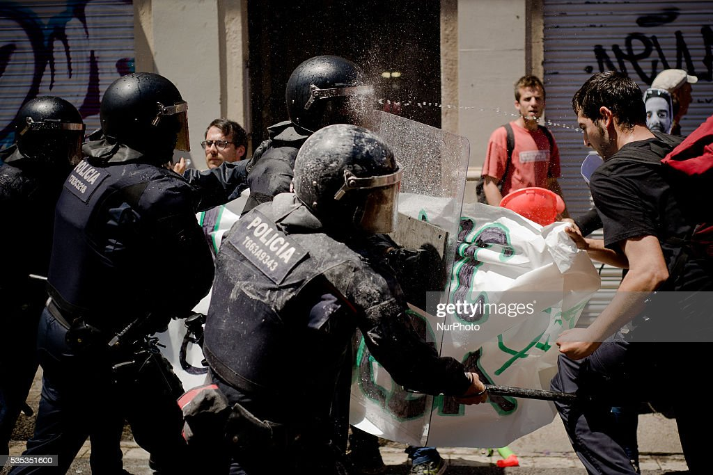A riot police officer's helmet is impacted by water jet thrown by protesters attempting to access the area of the Banc Expropiat on 29 May, 2016 in Barcelona (Spain). Tense Sunday in the streets of the popular Gracia district of Barcelona. After the eviction of an occupied bank branch known as the Banc Expropiat (Expropiated Bank) on past Monday 23 riots have been happening following days. Today hundreds of protesters tried to enter the building again guarded by riot police officers.