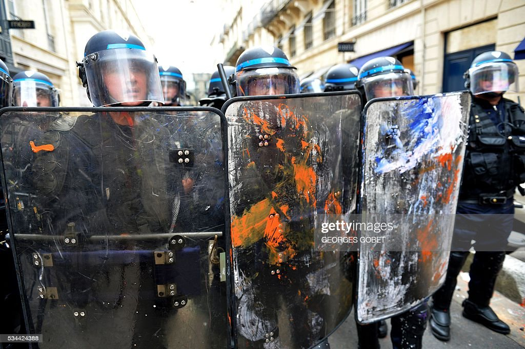 Riot police officers hold shields covered in paint during a protest called by seven labour unions and students against labour and employment law reform on May 26, 2016 in Bordeaux, southwest France. Fresh rallies were due to be held May 26 in Paris and other cities in the latest bout of social unrest that started three months ago and has frequently turned violent. Under intense pressure, Prime Minister Manuel Valls vowed the labour law would not be withdrawn, but said it might still be possible to make 'changes' or 'improvements'. / AFP / GEORGES
