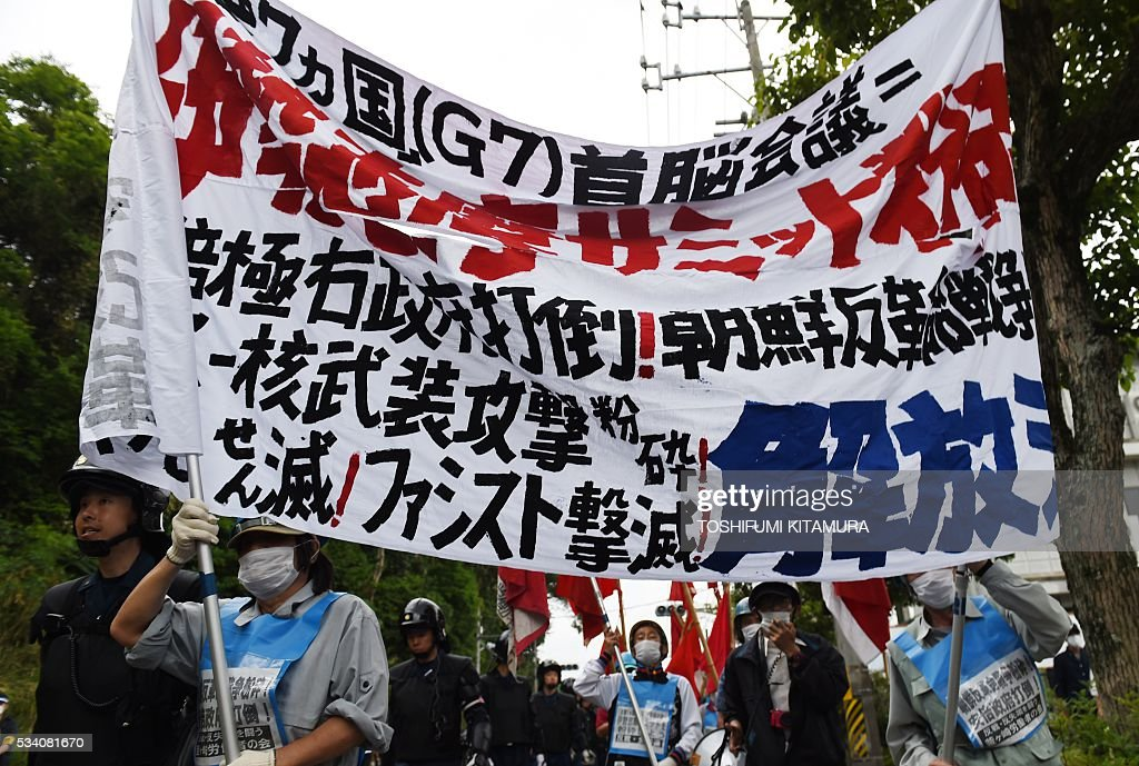 Riot police officers lead some 28 anti-G7 summit protesters as they stage a demonstration march in Shima city, Mie prefecture on May 25, 2016. Japan is on high-alert ahead of a Group of Seven summit with thousands of police on the streets of Tokyo and fanning out across the country as authorities boost security to unprecedented levels. / AFP / TOSHIFUMI