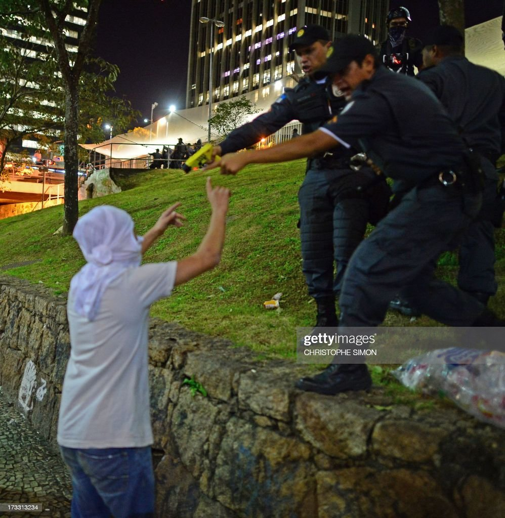 Riot police officers point at a demonstrator with a taser, an electroshock weapon, during clashes which erupted after a march by Brazilian workers in Rio de Janeiro on July 11, 2013 in a day of industrial action called by major unions to press demands for better work conditions. Demonstrators on Thursday blocked roads and staged protest rallies across the country on the 'National Day of Struggles' which was called by the country's five leading labour federations during last month's mass street protests to demand better public services and an end to endemic corruption.