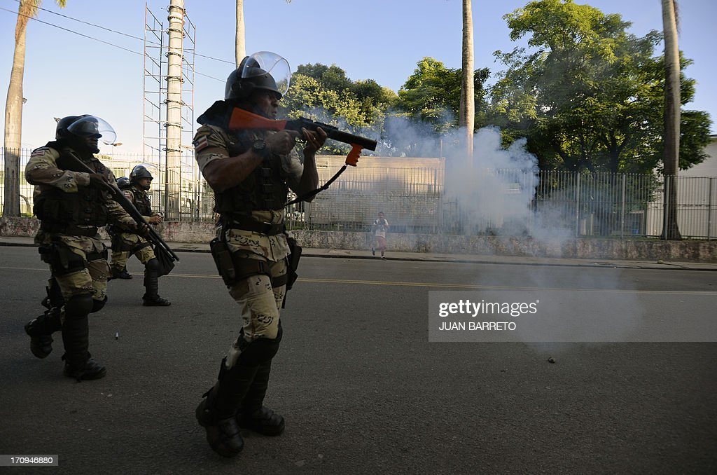 Riot police officers shoot rubber bullets to protesters who blocked access to the Arena Fonte Nova Stadium in Salvador, Bahia, where Nigeria is to play Uruguay in a FIFA Confederations Cup Brazil 2013 football match, during a protest of what is now called the 'Tropical Spring' against corruption and price hikes. Brazilians took to the streets again Thursday in several cities on a new day of mass nationwide protests, demanding better public services and bemoaning massive spending to stage the World Cup. More than one million people have pledged via social media networks to march in 80 cities across Brazil, as the two-week-old protest movement -- the biggest seen in the South American country in 20 years -- showed no sign of abating. AFP PHOTO / JUAN BARRETO