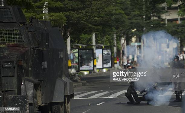 Riot police officers shoot tear gas at demonstrators during clashes which erupted after a march in support of Colombian farmers protesting in demand...
