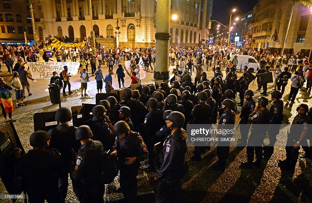 Riot police officers stand by as clashes erupt after a march by Brazilian workers in Rio de Janeiro on July 11, 2013 in a day of industrial action called by major unions to press demands for better work conditions. Demonstrators on Thursday blocked roads and staged protest rallies across the country on the 'National Day of Struggles' which was called by the country's five leading labour federations during last month's mass street protests to demand better public services and an end to endemic corruption.