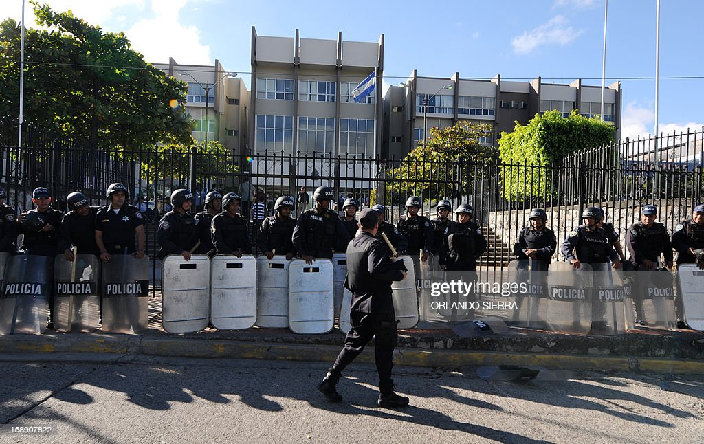 Riot police officers stand guard around the Supreme Court of Justice in Tegucigalpa, on January 3, 2013 as members of the National Confederation of Federations and Patrons of Honduras (Conafeph) demand the destitution of all the members of the Supreme Court. The head of Honduras' National Commission for Human Rights (CONADEH), Ramon Custodio, announced on Thursday he had asked the Inter-American Commission for Human Rights for preventive measures for the four judges who were removed by the Congress in December 2012 after they declared unconstitutional a purge plan at the police, deeply infiltrated by the organized crime. AFP PHOTO/Orlando SIERRA