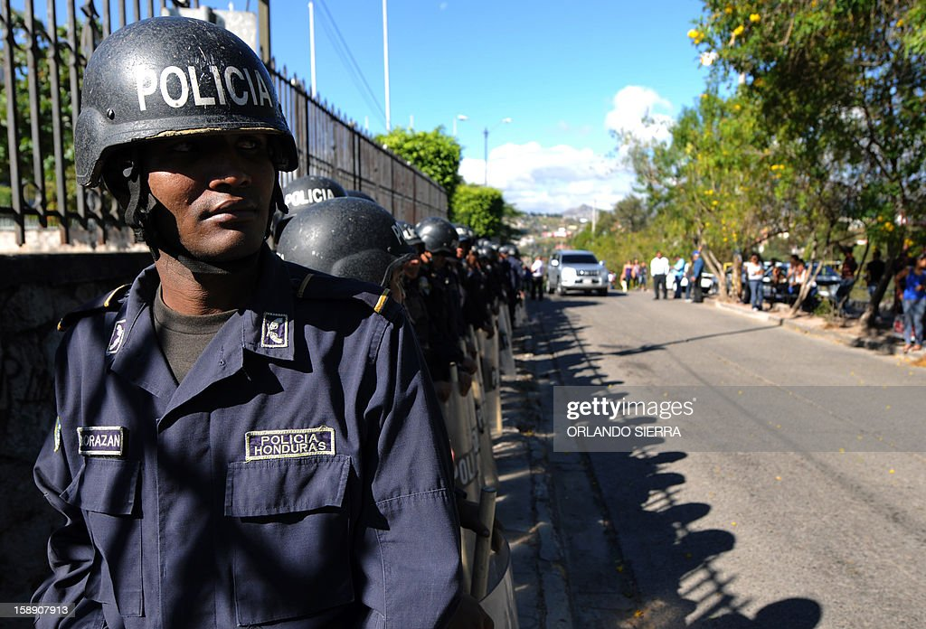Riot police officers stand guard around the Supreme Court of Justice in Tegucigalpa, on January 3, 2013 as members of the National Confederation of Federations and Patrons of Honduras (Conafeph), demand the destitution of all the members of the Supreme Court. The head of Honduras' National Commission for Human Rights (CONADEH), Ramon Custodio, announced on Thursday he had asked the Inter-American Commission for Human Rights for preventive measures for the four judges who were removed by the Congress in December 2012 after they declared unconstitutional a purge plan at the police, deeply infiltrated by the organized crime. AFP PHOTO/Orlando SIERRA