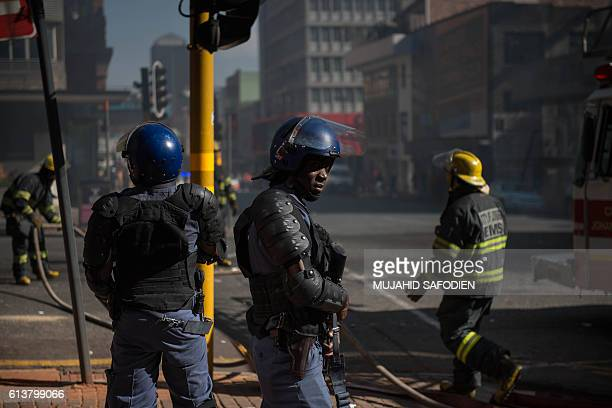 Riot police officers stand guard as firefighters are at work to put out a burning bus during clashes with students following a protest over...