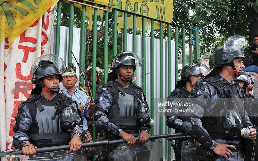 Riot Police officers stand guard at the entrance of the old indigenous museum --aka Aldea Maracana-- next to Maracana stadium in Rio de Janeiro on January 12, 2013. Indians have been occupying the place since 2006 as a protest against Rio de Janeiro's governmet decision to throw them out and pull down the building to construct 10,500 parking lots for the upcoming Brazil 2014 FIFA World Cup. AFP PHOTO/VANDERLEI ALMEIDA