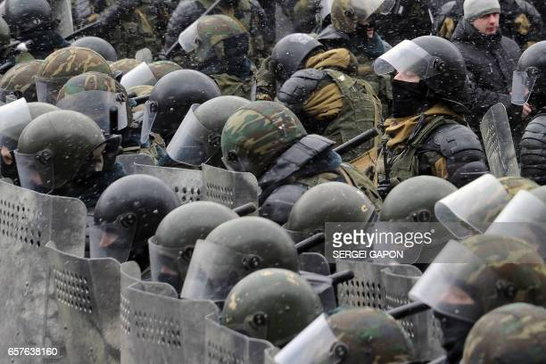 TOPSHOT Riot police officers stand guard during an opposition rally against President Alexander Lukashenko's rule and a controversial new tax on...