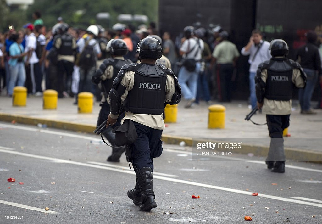 Riot police officers walk in downtown Caracas on March 21, 2013 during a demonstration of opposition students demanding to the National Electoral Council (CNE) transparency during the presidential elections next February 14.