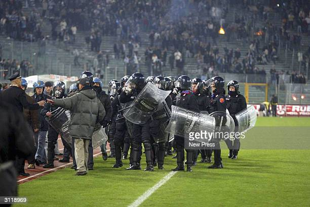Riot police on the pitch during the Serie A match between Roma and Lazio at the Stadio Olimpico on March 21 2004 in Rome Italy The Game was abandoned...