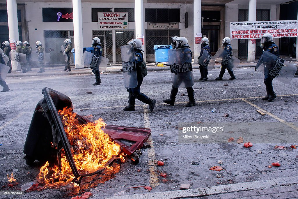 Riot police pass by burning barricades set by Greek farmers during a protest against planned pension reforms outside the Agriculture ministry on February 12, 2016 in Athens, Greece. Around reportedly 800 protesters from Crete gathered outnumbering police who were armed with teargas.