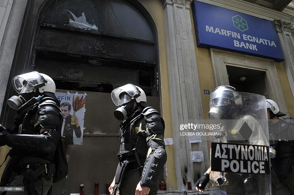 Riot police pass the burnt Marfin Bank during the protest march marking the 24-hour general strike against the austerity measures on May 20, 2010.Thousands of protesters took to the streets of Athens and second city Thessaloniki on Thursday in a new general strike against the government's debt-dictated austerity spending cuts and pension reform. AFP PHOTO / Louisa Gouliamaki