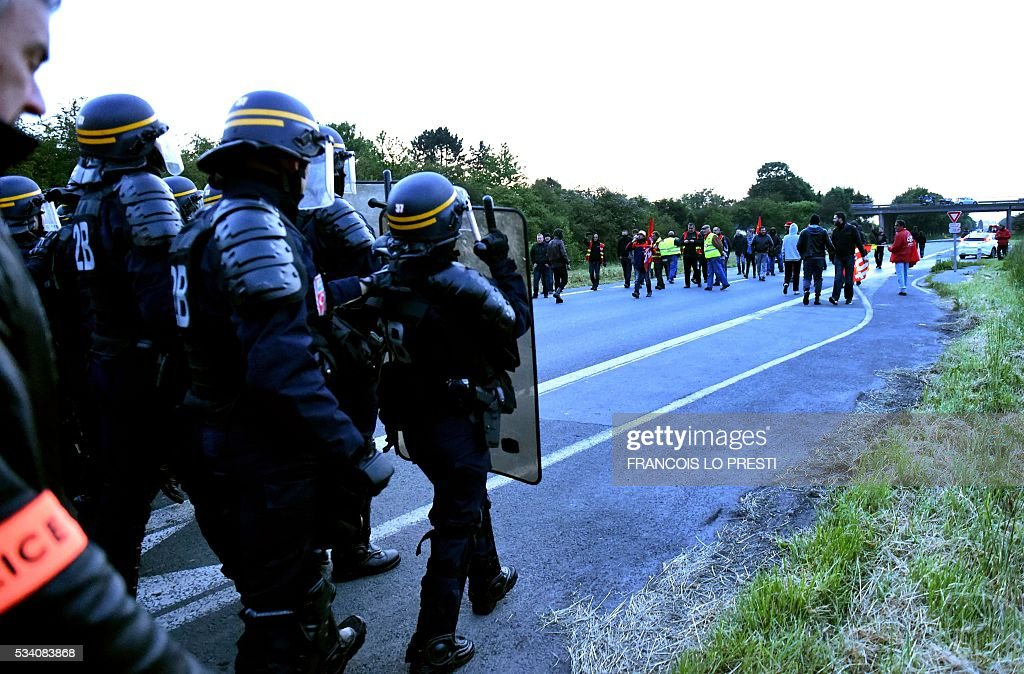 Riot police prepare to intervene to disperse refinery worker holding a blockade of the oil depot of Douchy-Les-Mines to protest against the government's proposed labour reforms, on May 25, 2016. Refinery workers stepped up strikes that threaten to paralyse France weeks ahead of the Euro 2016 tournament as the government moved to break their blockades, escalating a three-month tug-of-war over labour reforms. / AFP / FRANCOIS