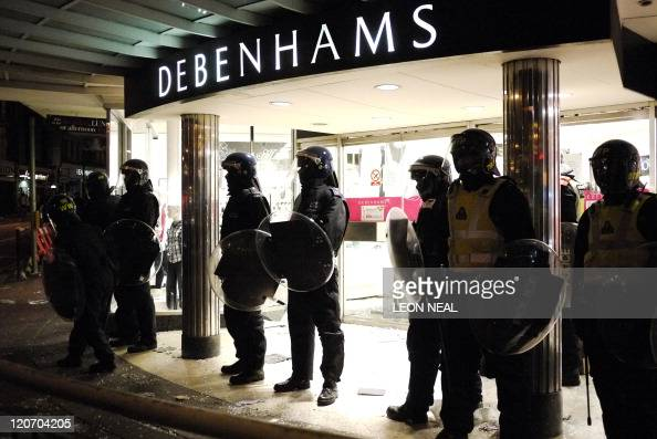 Riot police protect the entrance to Debenhams department store in Clapham Junction south London on 8 August 2011 Now in it's third night of unrest...