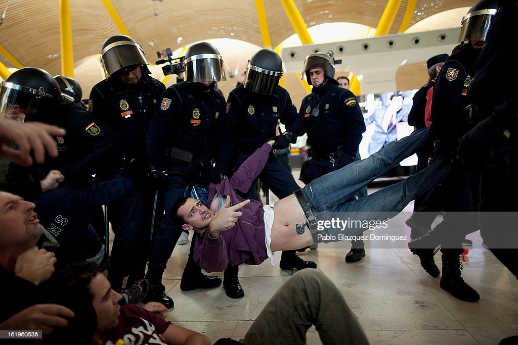 Riot police pull at a worker protesting from Spanish Airline Iberia during a rally against job cuts at Barajas Airport on February 18, 2013 in Madrid, Spain. Today is the first of a five day strike held by Iberia cabin crew, maintenance workers and ground staff in response to the planned loss of 3,800 jobs. The strike has resulted in the airline having to cancel 400 flights this week with unions planning a further five day strikes within a month.