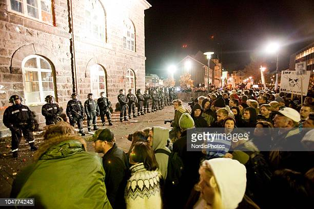 Riot police put up steel fences and stand guard in front of the Icelandic Parliament house as thousands of people are protesting the governments...