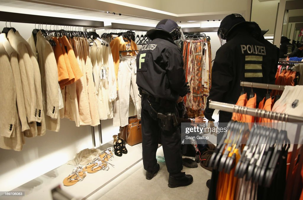 Riot police question a young man who had been among Blockupy protesters who had stormed into a Zara clothing store in the Zeil pedestrian shopping street on May 31, 2013 in Frankfurt am Main, Germany. Several thousand protesters are taking part in Blockupy protests today and tomorrow in Frankfurt in order to demonstrate aginst ECB debt policy, food prices speculation by Deutsche Bank and the labor practices inherent in the discount clothing industry.