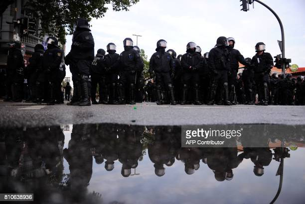 Riot police reflect in a puddle during protests in Hamburg's Schanzenviertel district on July 7 2017 in Hamburg northern Germany where leaders of the...