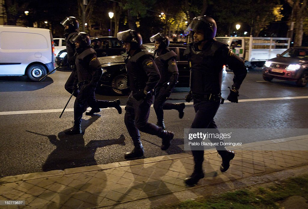 Riot police run behind protesters near Cibeles during demonstrations surrounding the Spanish Parliament on September 25, 2012 in Madrid, Spain. Demonstrators from various organizations, demanding a new constitutional process, are marching today from three different locations in the center of Madrid to the lower house in the Spanish parliament.