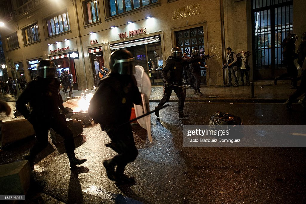 Riot police run over a barricade during clashes with protesters after a demonstration at Alcala Street on October 24, 2013 in Madrid, Spain. The Spanish Parliament recently approved a controversial reform of the educational system, which passed by the ruling right wing People's Party (PP) using their absolute majority and not backed by any other political party. The students are on a three day strike to protest against the new law, which will need to be approved by the senate next month and are calling for the resignation of Education Minister, Jose Ignacio Wert.