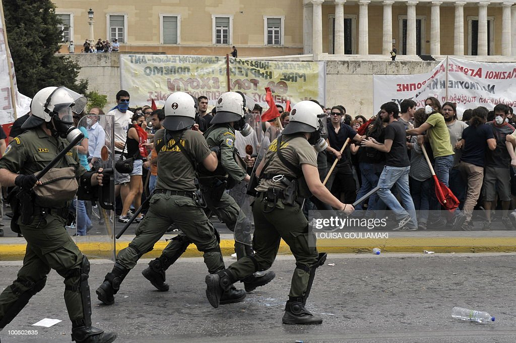 Riot police runs towards demonstrators outside the Greek parliament during the massive demonstration on May 5, 2010 in Athens.Three people were killed in a firebomb attack on a bank in central Athens on May 5 and around 20 people were evacuated from the building.