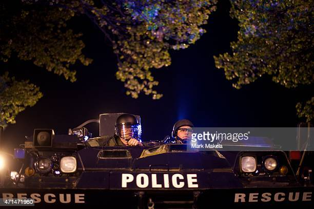 Riot police sit in an armored vehicle after the 10 pm imposed curfew the night following citywide riots over the death of Freddie Gray on April 28...