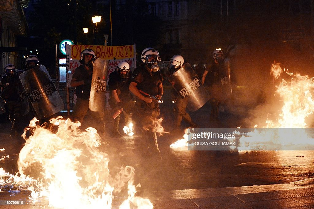 Riot police stand amid petrol bombs threw by protesters during an antiausterity protest on July 15 2015 Antiausterity protesters hurled petrol bombs...