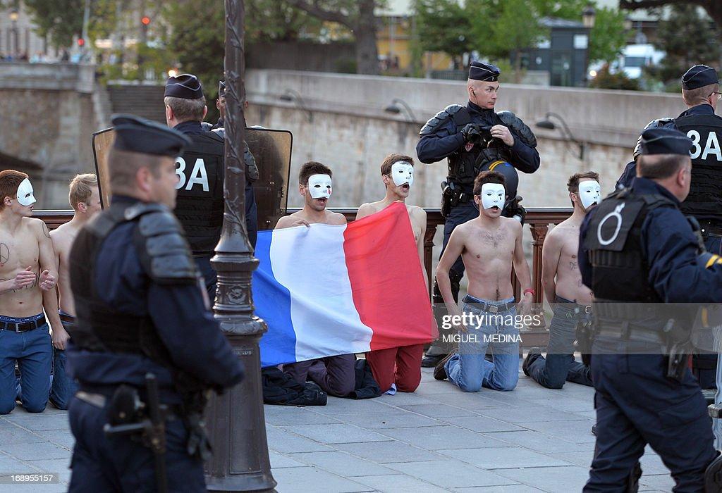 Riot police stand around bare-chested men wearing white masks and belonging to an anti-gay group (Hommen), as they demonstrate against a bill legalizing same sex marriages on May 17, 2013 in Paris. After months of acrimonious debate and hundreds of protests that have occasionally spilled over into violence, France's National Assembly approved on April 23, 2013 a bill making the country the 14th to legalise same-sex marriage. AFP PHOTO / MIGUEL MEDINA