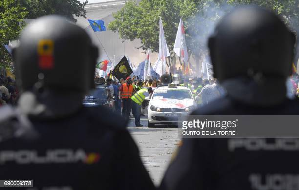 Riot police stand as taxi drivers march during a strike action held between Atocha Train station to Neptuno Square in Madrid on May 30 2017 against...