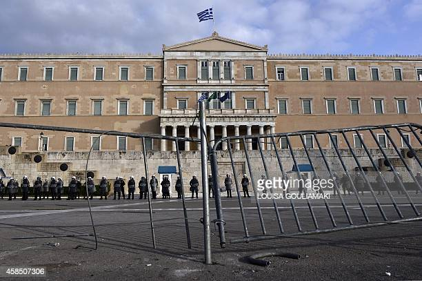 Riot police stand behind smashed barriers protecting the Greek parliament in central Athens on November 6 2014 during a students and pupils rally...