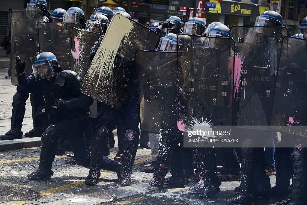 Riot police stand behind their shields during a demonstration against the government's planned labour reform, on May 26, 2016 in Lyon, central eastern France. The French government's labour market proposals, which are designed to make it easier for companies to hire and fire, have sparked a series of nationwide protests and strikes over the past three months. Masked youths clashed with police in Paris and striking workers blockaded refineries and nuclear power stations on May 26, 2016 as an escalating wave of industrial action against labour reforms rocked France. KSIAZEK