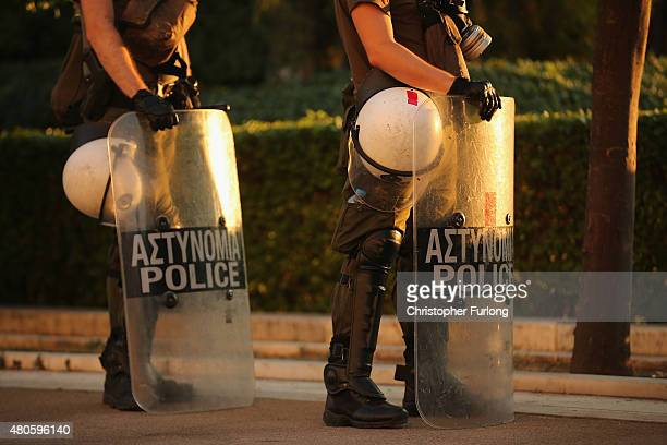 Riot police stand by as protesters gather outside the Greek parliament to demonstrate against austerity after an agreement for a third bailout with...