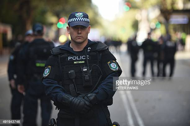 Riot police stand guard as antiMuslim protesters hold a demonstration outside the Parramatta Mosque in Sydney on October 9 2015 A small number of...