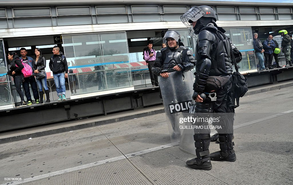 Riot police stand guard at the 'Transmilenio' station in southern Bogota, Colombia, on February 12, 2016. Users of public transportation blocked roads to protest what they consider poor service and high cost. Amid the protest several buses were damaged as well as stations destroyed and several demonstrators were detained by police after clashes. AFP PHOTO / GUILLERMO LEGARIA / AFP / GUILLERMO LEGARIA