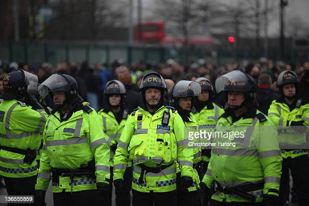 Riot police stand guard before the FA Cup Third Round match between Manchester City and Manchester United at the Etihad Stadium on January 8 2012 in...