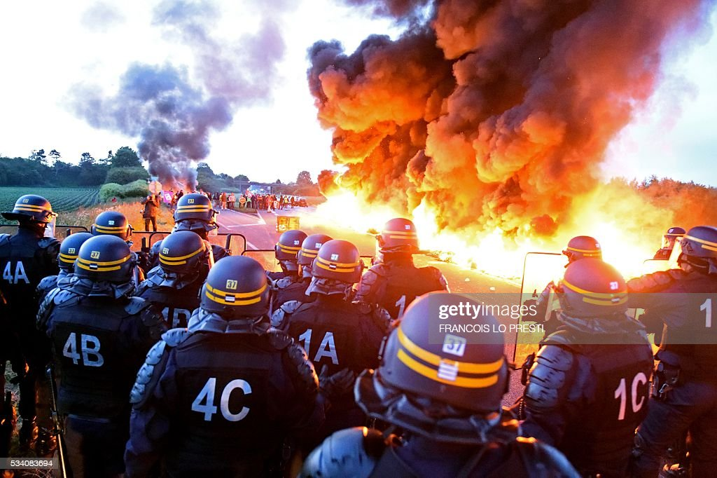 Riot police stand guard behind a fire as refinery workers hold a blockade of the oil depot of Douchy-Les-Mines to protest against the government's proposed labour reforms, on May 25, 2016. Refinery workers stepped up strikes that threaten to paralyse France weeks ahead of the Euro 2016 tournament as the government moved to break their blockades, escalating a three-month tug-of-war over labour reforms. / AFP / François LO