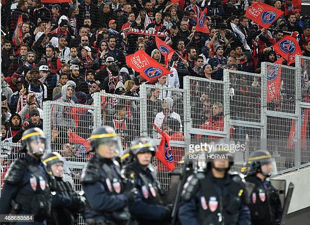 Riot police stand guard in front of Paris SaintGermain's supporters at the end of the French L1 football match between Marseille and Paris on April 5...