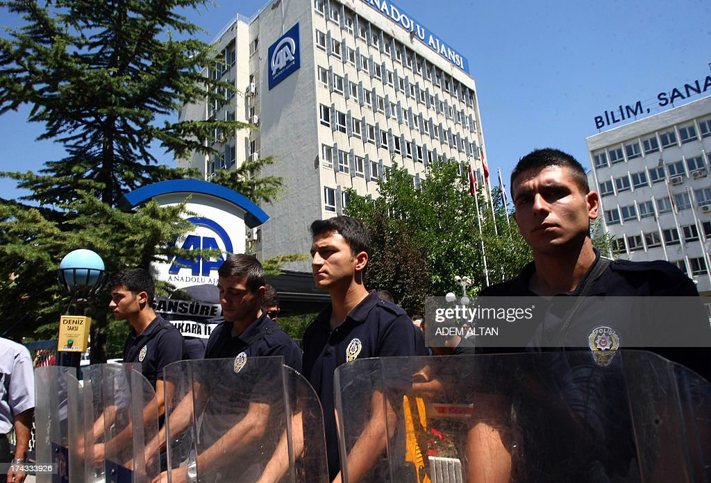 Riot police stand guard on July 24, 2013 outside the headquarters of Anadolu news agency in Ankara, as a group of journalists and members of the Republican People's Party protest against censorship in Turkish media on Journalism Day.