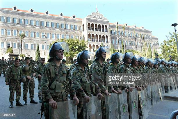 Riot police stand guard outside a government builing during a protest by Lebanese professors and students demonstrating 11 December 2003 in support...