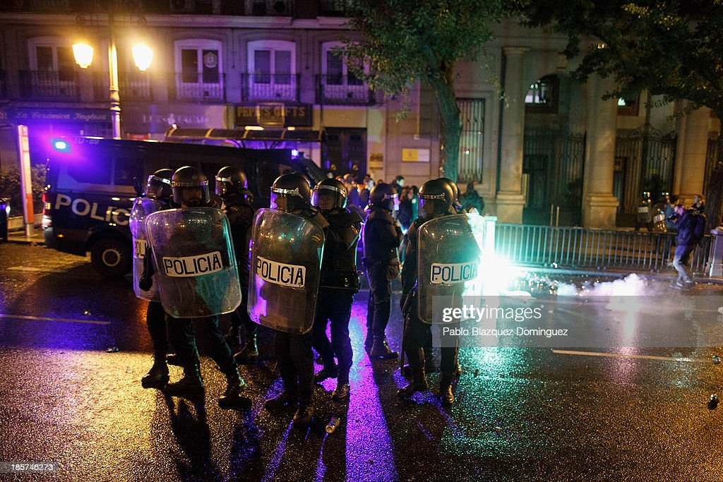 Riot police stand guard outside the Education Ministry during clashes with protesters after a demonstration at Alcala Street on October 24, 2013 in Madrid, Spain. The Spanish Parliament recently approved a controversial reform of the educational system, which passed by the ruling right wing People's Party (PP) using their absolute majority and not backed by any other political party. The students are on a three day strike to protest against the new law, which will need to be approved by the senate next month and are calling for the resignation of Education Minister, Jose Ignacio Wert.