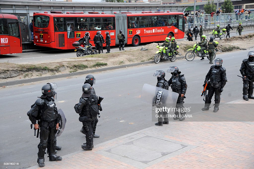 Riot police stand guard outside the 'Transmilenio' station in southern Bogota, Colombia, on February 12, 2016. Users of public transportation blocked roads to protest what they consider poor service and high cost. Amid the protest several buses were damaged as well as stations destroyed and several demonstrators were detained by police after clashes. AFP PHOTO / GUILLERMO LEGARIA / AFP / GUILLERMO LEGARIA