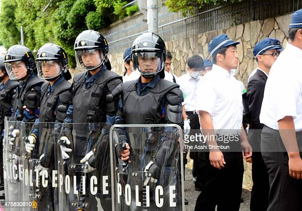Riot police stand guard while police officers enter the Japan's biggest Yakuza syndicate 'Yamaguchi Gumi' headquarters for a raid on June 3 2015 in...